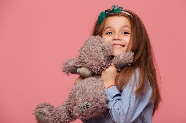 Szczęśliwa dziewczyna ma długie kasztanowe włosy uśmiecha się, grając z jej uroczym zabawkowym misiem