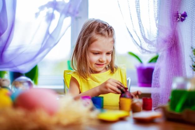 Szczęśliwa dziewczyna maluje pisanki, małe dziecko w domu zabawy. ferie wiosenne