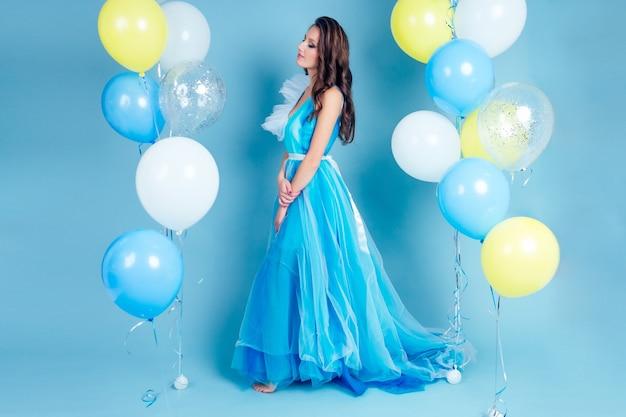 Szczęśliwa dziewczyna na balu z helem powietrza biały, niebieski i żółty balony. portret pięknej kobiety w niebieskiej sukience z mnóstwem kolorowych balonów w studio niebieskim tle. koncepcja wolności i świętowania