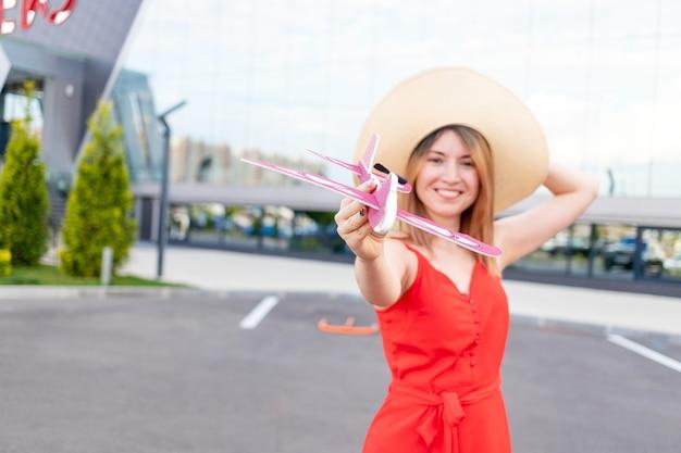 Szczęśliwa dziewczyna na lotnisku trzyma w dłoni samolot w czerwonej sukience i kapeluszu latem, koncepcja podróży lub wakacji, samolot jest w zbliżeniu w centrum uwagi