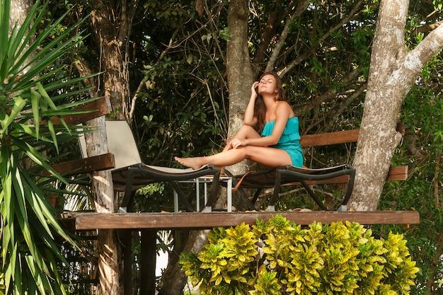 Szczęśliwa dziewczyna na platformie przy drzewem z sunbeds