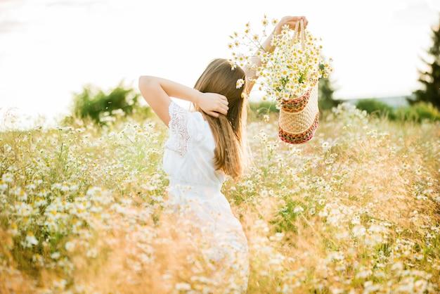 Szczęśliwa dziewczyna na polu rumianku, letni zachód słońca. w białej sukni. bieganie i kręcenie się, wiatr we włosach, styl życia. koncepcja wolności i gorące lato.