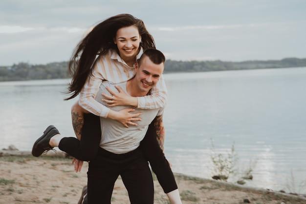 Szczęśliwa dziewczyna na ramionach swojego chłopaka uśmiechnięta i szczęśliwa w lecie w przyrodzie. zdjęcie jest rozmyte z powodu ruchu i krótkiego czasu otwarcia migawki