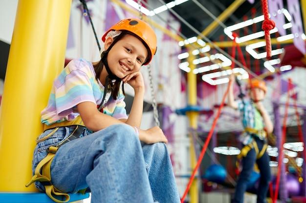 Szczęśliwa dziewczyna na terenie wspinaczkowym, dzieciaki spędzają weekend na placu zabaw, aktywne dzieciństwo