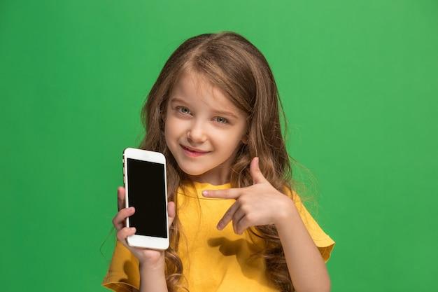 Szczęśliwa dziewczyna nastolatka stojąc i uśmiechając się na zielonym tle.