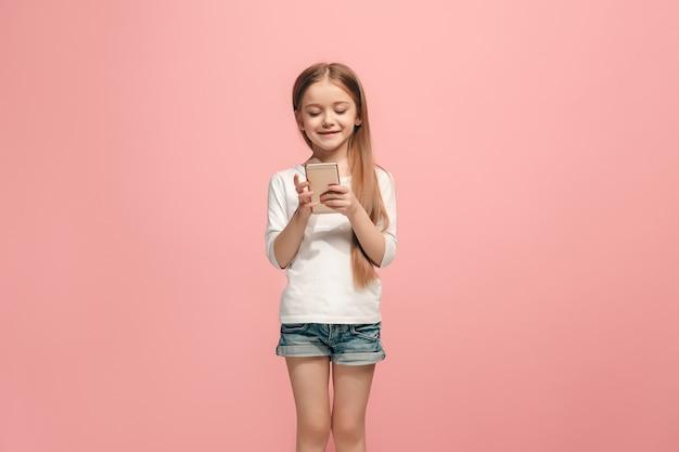 Szczęśliwa dziewczyna nastolatka stojąc i uśmiechając się przed różową ścianą