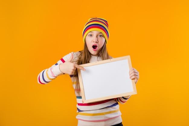Szczęśliwa dziewczyna nastolatka trzyma w rękach pustą deskę kreślarską. miejsce na tekst