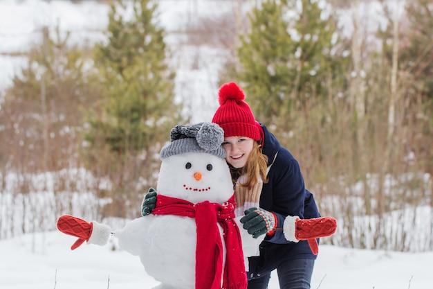 Szczęśliwa dziewczyna nastolatka z bałwana w zimowym lesie