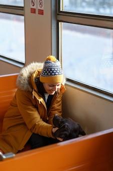 Szczęśliwa dziewczyna nosi zimowe ubrania siedząc w lokalnym pociągu rozmawiając ze swoim uroczym psem podróżującym razem