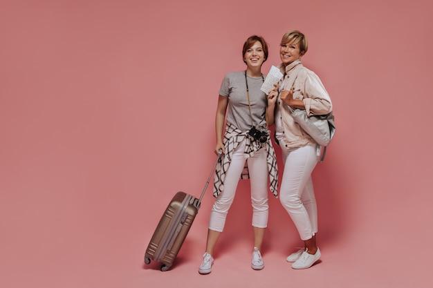 Szczęśliwa dziewczyna o ciemnych włosach w jasnych spodniach i szarym t-shircie trzyma walizkę, bilety i aparat fotograficzny i pozuje z uśmiechniętą kobietą na różowym tle.
