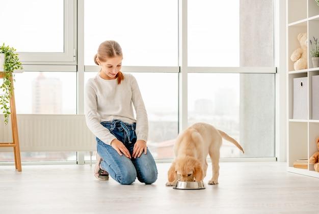 Szczęśliwa dziewczyna obok jeść szczeniaka