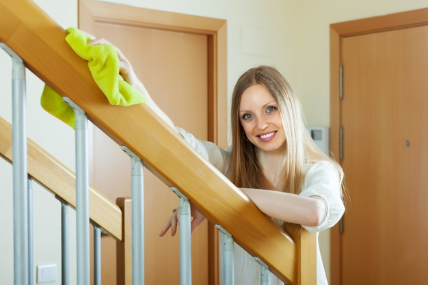 Szczęśliwa dziewczyna odkurzania poręczy schodów