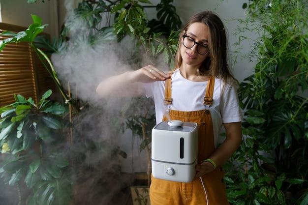 Szczęśliwa dziewczyna ogrodniczka używa nawilżacza powietrza w domu w krytym ogrodzie podczas sezonu grzewczego dla roślin