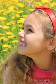 Szczęśliwa dziewczyna ono uśmiecha się w żółtym kwiatu ogródzie
