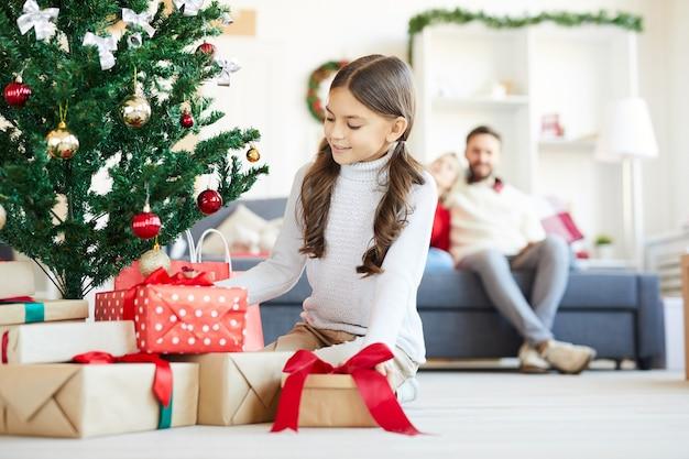 Szczęśliwa dziewczyna otwiera prezenty świąteczne