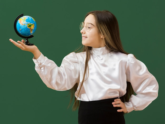 Szczęśliwa dziewczyna patrzeje kulę ziemską