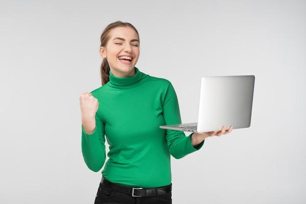 Szczęśliwa dziewczyna patrzeje laptop z śmiać się zdziwionego wyrażenie