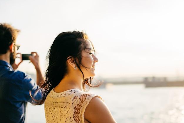 Szczęśliwa dziewczyna płynie statkiem po wodzie o zachodzie słońca, stoi plecami, cieszy się zachodem słońca, patrzy w dal