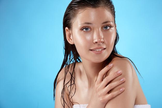 Szczęśliwa dziewczyna po prysznic z mokrymi włosami, uśmiechając się na białym tle na niebiesko