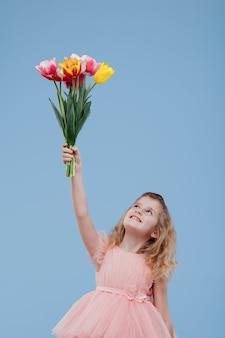 Szczęśliwa dziewczyna podnosząc ręce z bukietem kwiatów