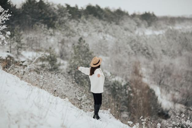 Szczęśliwa dziewczyna podróżnik z rękami stojąc na szczycie góry i patrząc na piękny zimowy śnieżny krajobraz.