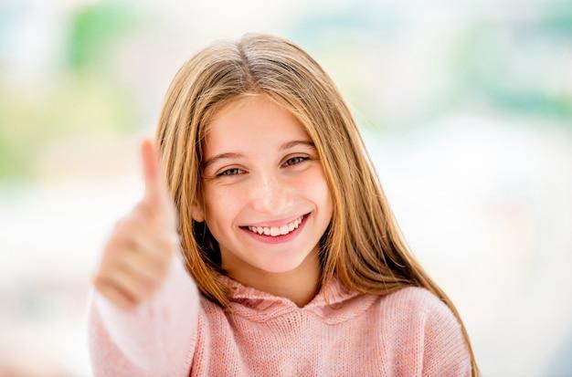 Szczęśliwa dziewczyna pokazuje kciuk up