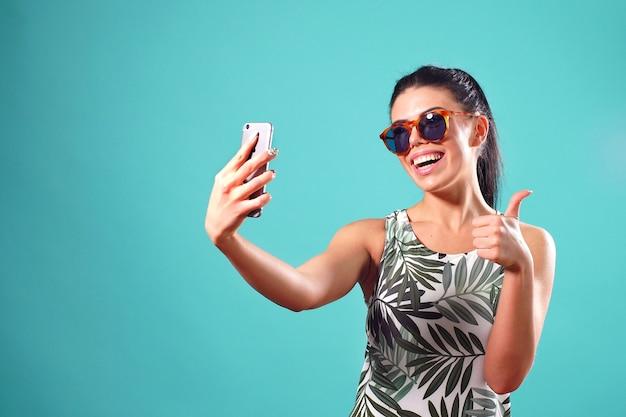 Szczęśliwa dziewczyna pozuje w studiu bierze selfie na telefonie