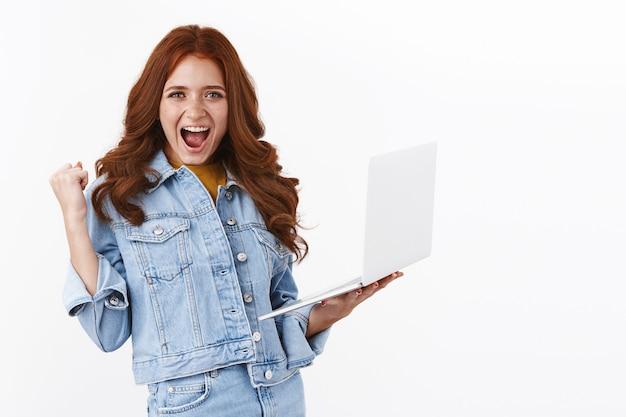 Szczęśliwa dziewczyna przechodzi poziom gry na laptopie, trzymając notatnik i wesoło pompując pięścią, uśmiechając się z ulgą, osiągając cel, krzycząc hura tak jak triumf, świętując osiągnięcie, biała ściana