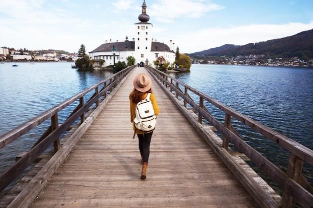 Szczęśliwa dziewczyna przechodzi przez most do zamku ort, austria