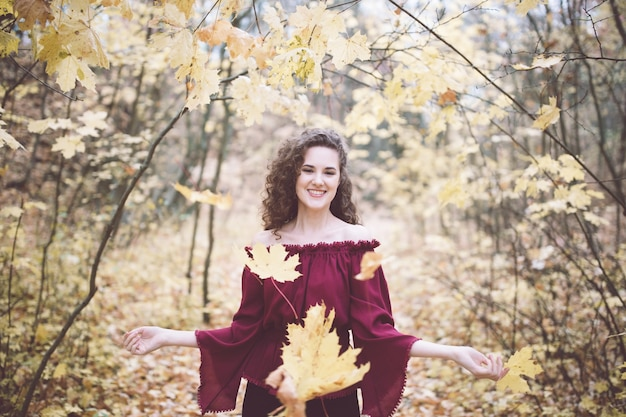 Szczęśliwa dziewczyna rzuca liście klonowych w atumn parku