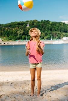 Szczęśliwa dziewczyna rzuca piłkę wiatru