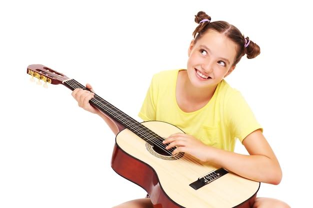 Szczęśliwa dziewczyna siedząca na białym tle z gitarą