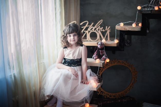 Szczęśliwa dziewczyna siedzi na schody ozdobione girlandą
