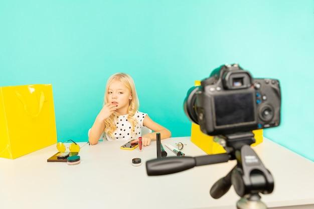 Szczęśliwa dziewczyna siedzi przy biurku w niebieskim studio, mówiąc przed kamerą na vlog. młoda blogerka kosmetyczna nagrywa samouczek wideo do internetu.
