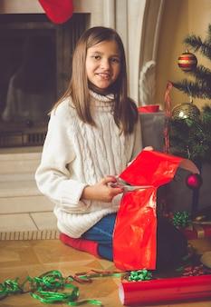 Szczęśliwa dziewczyna siedzi przy kominku i pakuje świąteczne prezenty