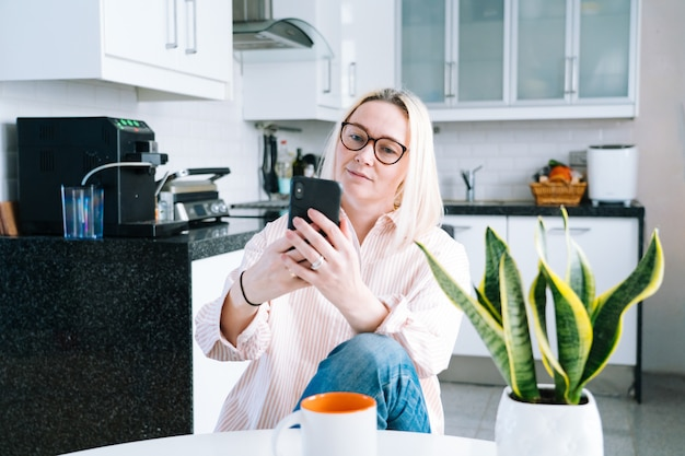 Szczęśliwa dziewczyna siedzi w domu kuchnię i trzyma połączenie wideo. młoda kobieta używa smartphone dla rozmowy wideo z przyjacielem lub rodziną. webinarium z nagraniem vloggera. kobiety przyglądająca kamera i machać powitanie ręki