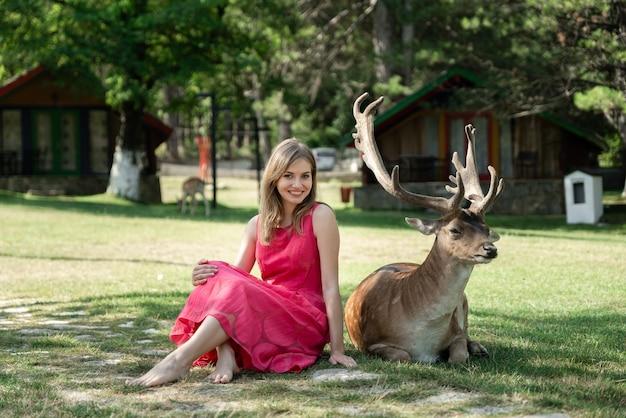 Szczęśliwa dziewczyna siedzi w pobliżu jelenia w parku