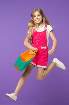 Szczęśliwa dziewczyna skok z torbą na zakupy na fioletowym tle. mały uśmiech dziecka z papierową torbą. klientka w modnym kombinezonie. przygotowanie i świętowanie wakacji. zakupy i czarny piątek.