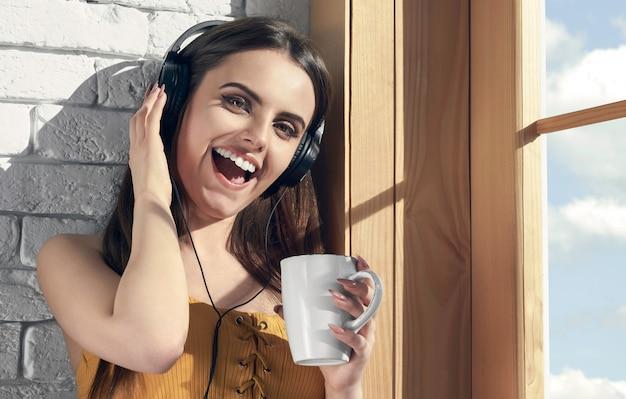 Szczęśliwa dziewczyna słucha muzyka i trzyma białego kubek obok okno w ranku
