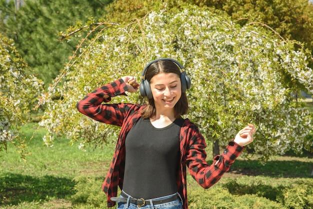 Szczęśliwa dziewczyna, słuchanie muzyki na słuchawkach i taniec w parku