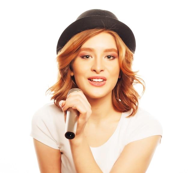 Szczęśliwa dziewczyna śpiewa. piękna kobieta ubrana w białą koszulkę i czarny kapelusz z mikrofonem na białym tle. styl hipsterski.