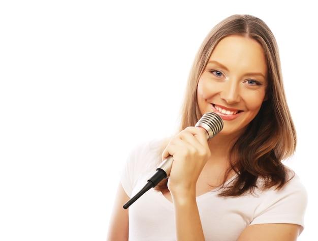 Szczęśliwa dziewczyna śpiewa. piękna kobieta ubrana w białą koszulkę z mikrofonem na białym tle.