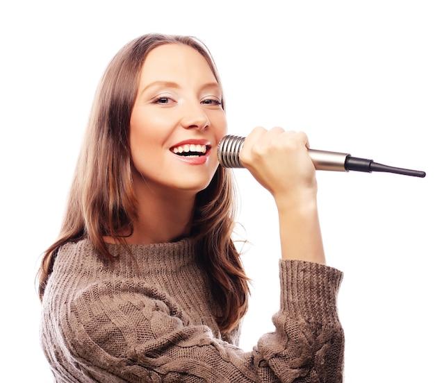 Szczęśliwa dziewczyna śpiewa. piękna kobieta z mikrofonem na białym tle.