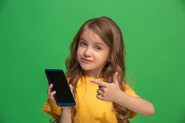 Szczęśliwa dziewczyna stoi i uśmiecha się z telefonem komórkowym