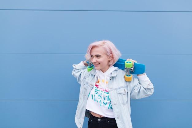 Szczęśliwa dziewczyna stoi z deskorolką na powierzchni niebieskiej ściany i uśmiecha się