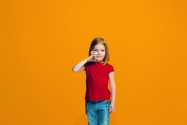Szczęśliwa dziewczyna stojąc i uśmiechając się przed pomarańczową ścianą