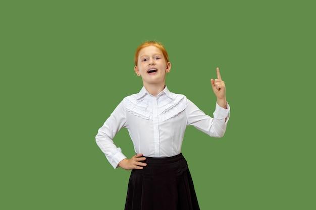 Szczęśliwa dziewczyna stojąc, uśmiechając się i wskazując w górę na białym tle na modnym zielonym tle studio. piękny portret kobiety w połowie długości.