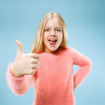 Szczęśliwa dziewczyna stojąc, uśmiechając się na białym tle na modnym niebieskim tle studio. piękny portret kobiety. młoda dziewczyna zadowala ze znakiem ok. ludzkie emocje, koncepcja wyrazu twarzy. przedni widok.
