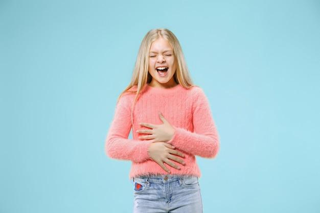Szczęśliwa dziewczyna stojąc, uśmiechając się na białym tle na modnym niebieskim tle studio. piękny portret kobiety.