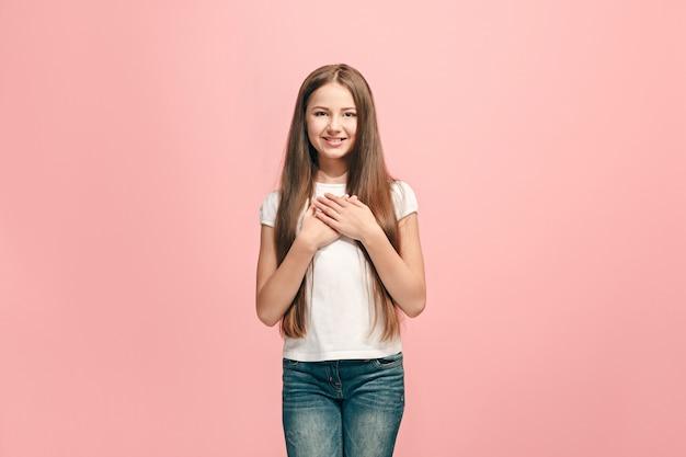 Szczęśliwa dziewczyna stojąc, uśmiechając się na białym tle na modnym różowym studio